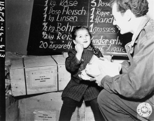 Harry Weinsaft of the American Jewish Joint Distribution Committee, gives food to three-year-old Renati Rulhater, a Jewish DP child in Vienna, Austria, 1945.